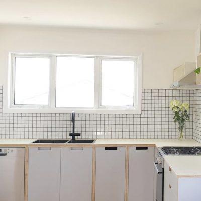 White plywood kitchen with black sink